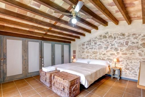 Eine stylische Natursteinwand dekoriert das Schlafzimmer