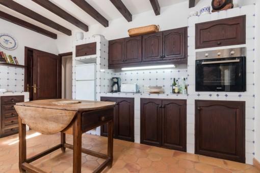 Die Küche hat Holzschränke und tolle Fliesen