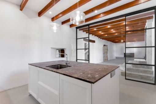 Angrenzende Küche mit Kochinsel