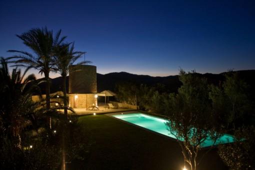 Beleuchteter Poolbereich und Garten