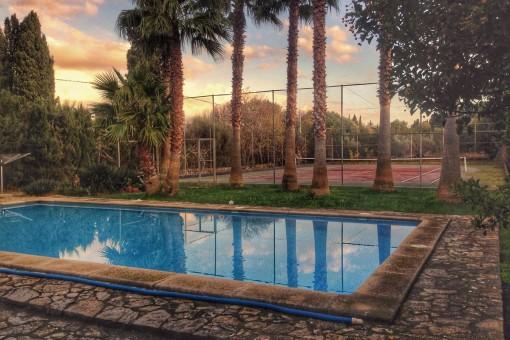 Blick über den Swimmingpool auf den Tennisplatz