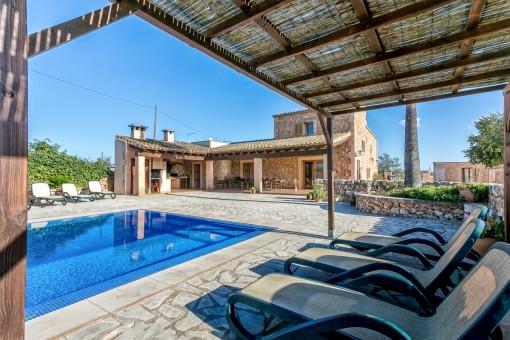 Überdachter Entspannungsbereich neben dem Pool