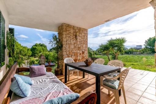 Schöner Sitzbereich unter der überdachten Terrasse mit Gartenblick