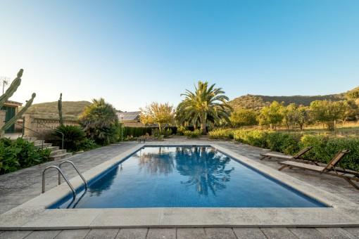 Idyllischer Poolbereich mit Sonnenliegen