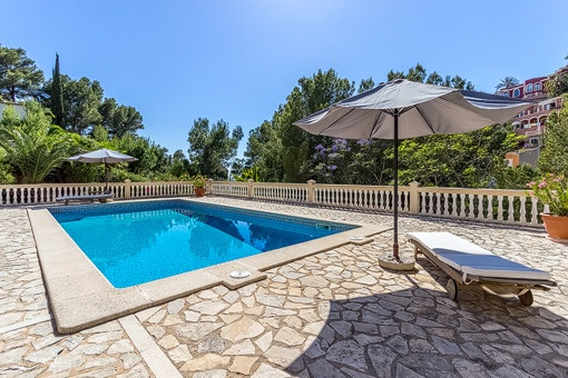 Der Swimmingpool ist von einer Terrasse umgeben
