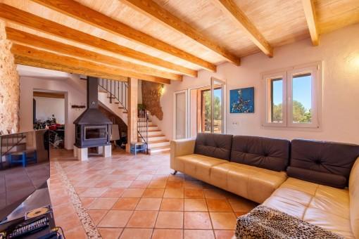 Gemütlicher Wohnbereich mit Kamin und hohen Decken mit Holzbalken