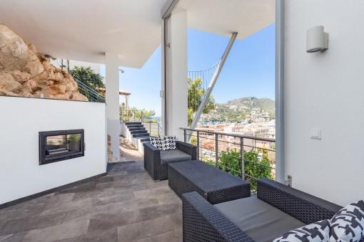 Loungeecke auf der überdachten Terrasse mit Kamin