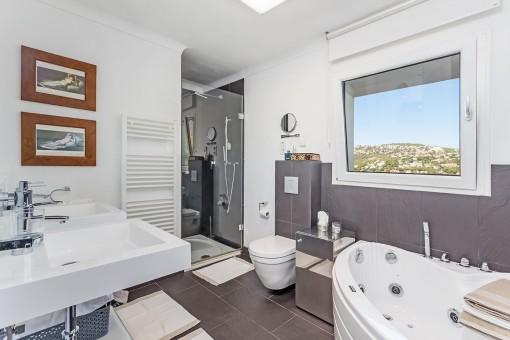 Einladendes Hauptbadezimmer mit Badewanne und Dusche