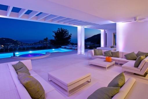 Blick vom Loungebereich auf den Swimmingpool bei Nacht
