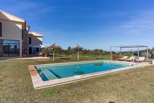 Swimmingpool ist von einer Rasenfläche umgeben