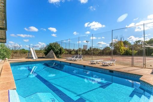 Fantastischer Poolbereich mit Sonnenliegen neben dem Tennisplatz