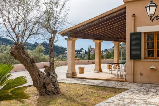 Blick auf die überdachte Terrasse vom Garten aus
