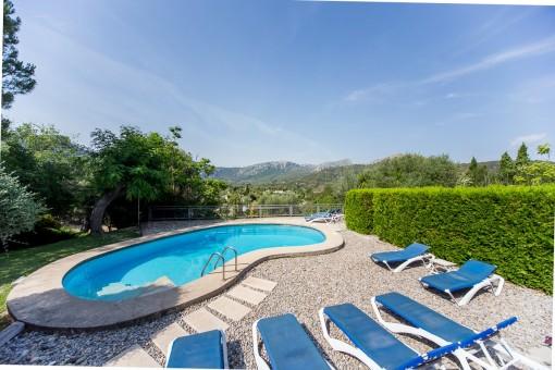 Der Swimmingpool ist von einer Terrasse mit Liegestühlen umgeben