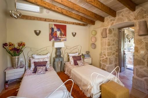 Schlafzimmer mit zwei getrennten Betten und Natursteinwand