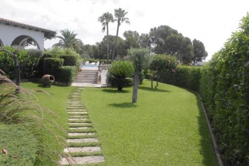Ein Weg führt durch den Garten zur Villa
