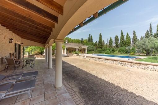 Blick von der überdachten Terrasse auf den Swimmingpool
