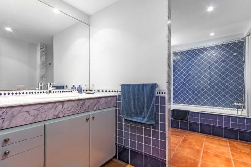 Blaues Badezimmer mit großem Spiegel