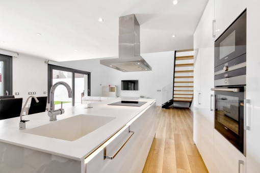 Voll ausgestattete, offene Einbauküche mit Kochinsel
