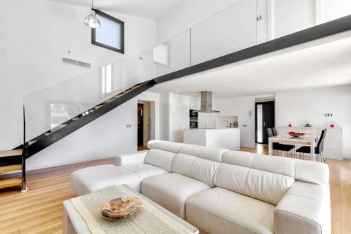 Eine Treppe mit Glasgeländer führt ins obere Stockwerk