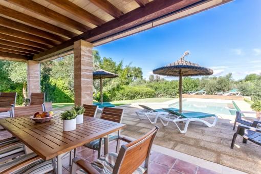 Sitzgelegenheit auf der überdachten Terrasse mit Blick auf den Pool