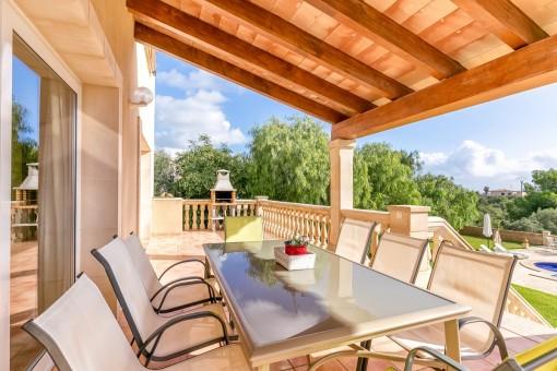 Überdachte Terrasse mit Sitzgelegenheit und Grill