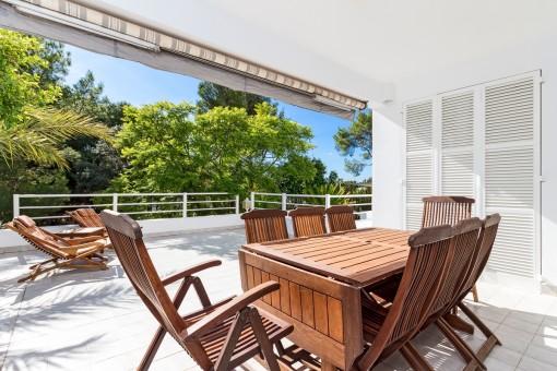 Teilweise überdachte Terrasse mit gemütlicher Sitzgelegenheit