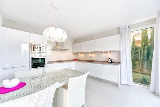 Die weiße Küche is voll ausgestattet mit guten Geräten