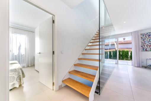 Eine elegante Treppe mit Glaswand führt in den oberen Stock