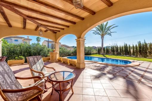 Entspannungsbereich auf der überdachten Terrasse mit Blick in den Garten und auf den Pool