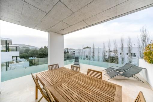 Überdachte Terrasse mit Sitzbereich und Sonnenliegen