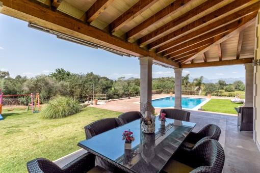 Überdachte Terrasse mit Essbereich und Poolblick