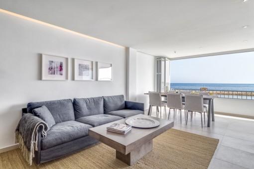 Wohn-und Essbereich mit offener Fensterfront und Meerblick