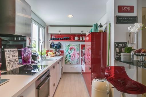 Voll ausgestattete Küche mit roten Elementen