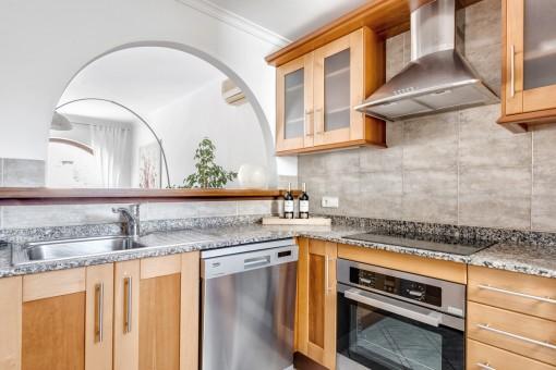 Voll ausgestattete Küche mit Durchreiche zum Wohnbereich