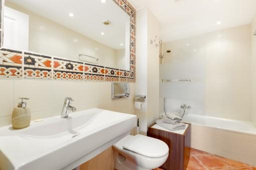 Freundliches Badezimmer mit Badewanne