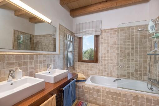 Charmantes Badezimmer mit Doppelwaschbecken und Badewanne