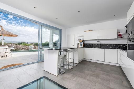 Moderne und voll ausgestattete Küche mit Terrassenzugang