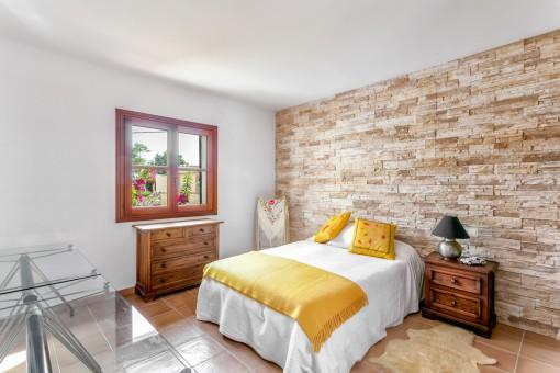 Doppelschlafzimmer mit Steinwand