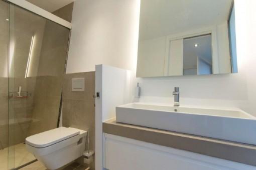 Ein weiteres Badezimmer im minimalischen Design mit ebenerdiger Dusche