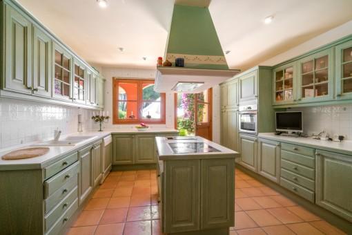 Küche mit Kochinsel und Hauswirtschaftsraum