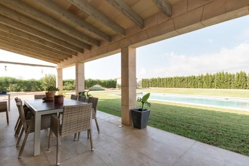 Überdachte Terrasse mit Poolblick