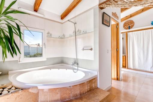Badezimmer mit großer Badewanne und Ankleidebereich