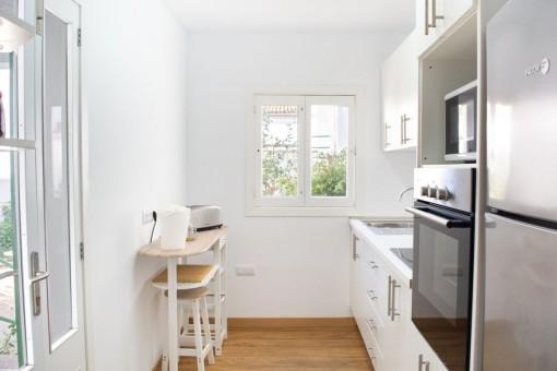 Weiße Küche mit Terrassenzugang